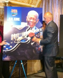 Allen Naples, Syracuse president of title sponsor M&T Bank, turns over the poster revealing B.B. King as the festival's July 12 headliner.