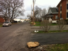 Four neighbors in a line have completed spring cleanup in the yard and left bags for recycling.