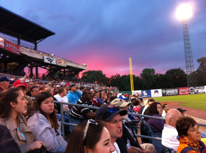 Over the left field stands, a pretty sunset.