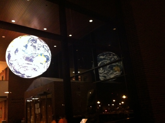 The earth exhibit shines inside the Heroy Geology Building and its windows Friday night on the Syracuse University campus.