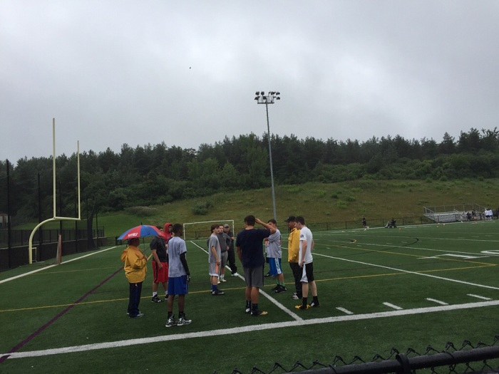 Football players work out on a rainy July night at Christian Brothers Academy.