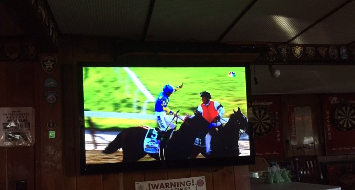 A flat screen in a Cape Cod joint captures Victor Espinoza on American Pharoah celebrating the Triple Crown.
