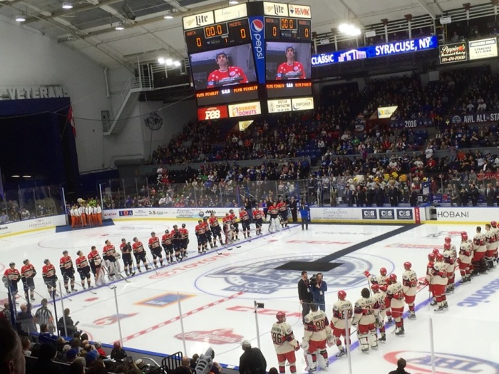 The players are at attention, ready to play, as Syracuse Crunch captain Mike Angelides is announced last.